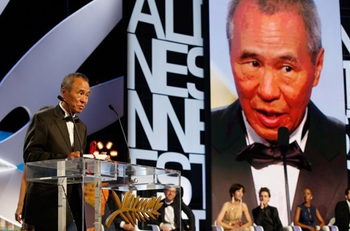 Taiwanese director Hou Hsiao-Hsien talks on stage after being awarded with the Best Director prize during the closing ceremony of the 68th Cannes Film Festival in Cannes, southeastern France, on May 24, 2015.   AFP PHOTO / VALERY HACHE